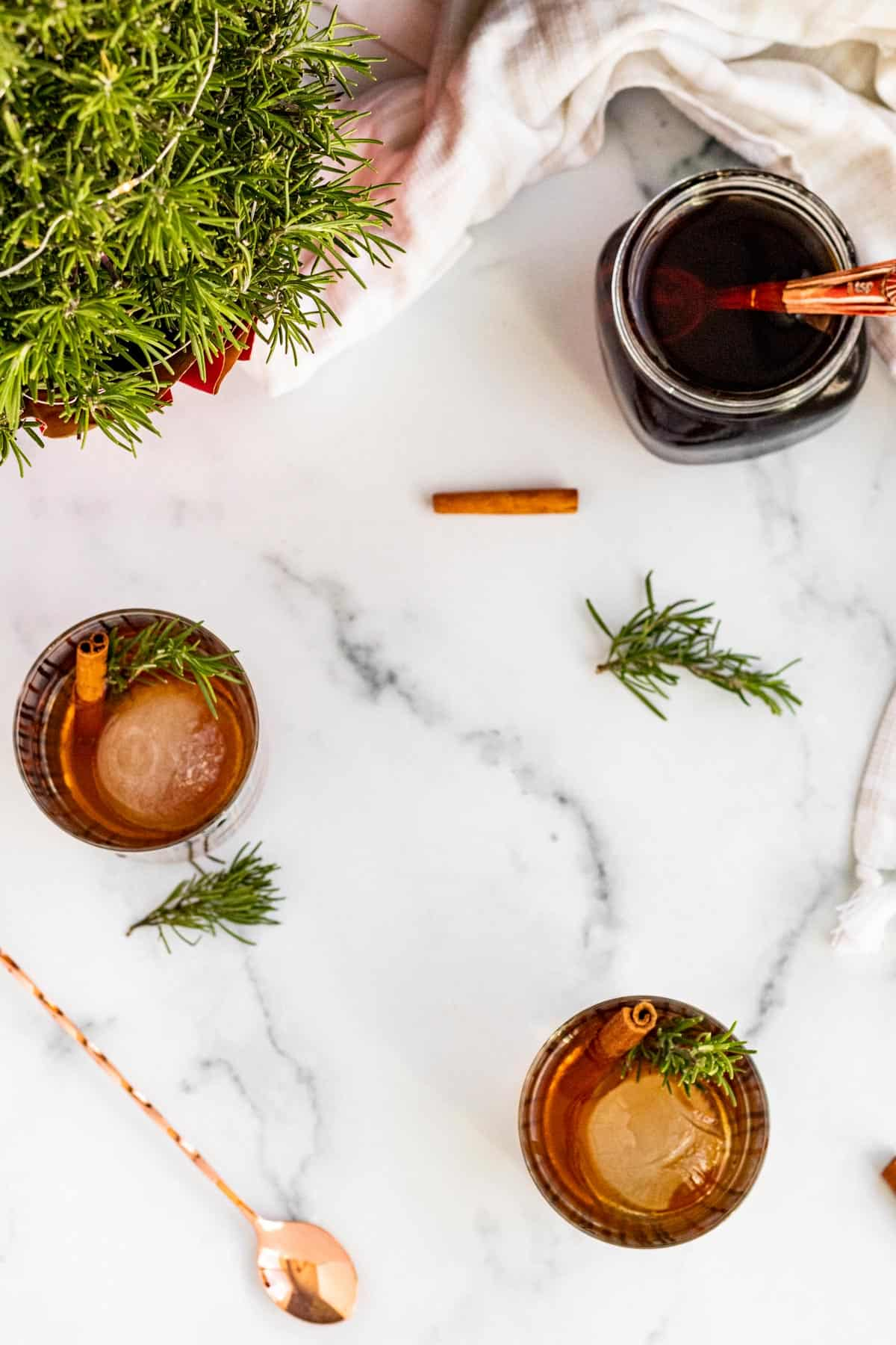 overhead view of 2 bourbon cocktails with sprigs of rosemary and cinnamon sticks for garnish