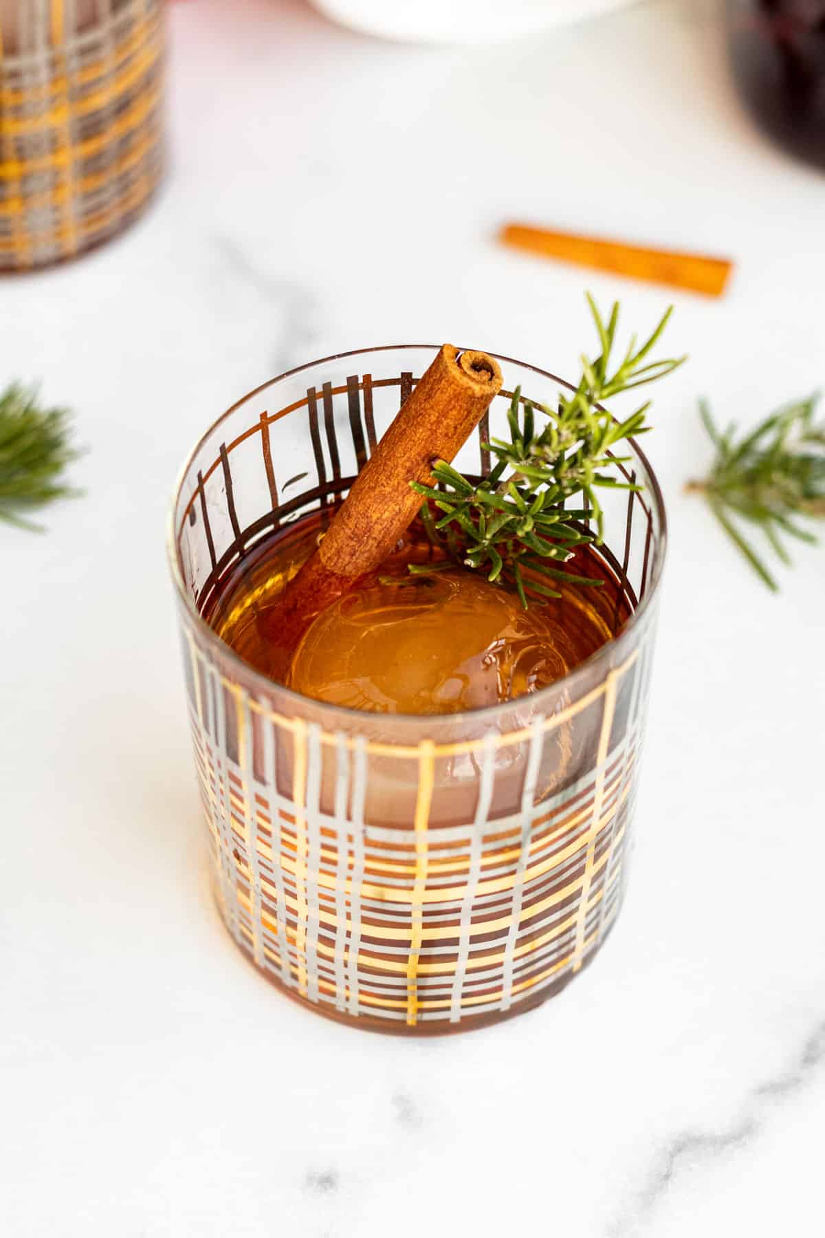 cocktail glass with a clear ice ball and winter old fashioned garnished with rosemary and cinnamon stick sitting on marble counter