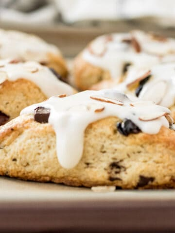 chocolate cherry almond scone with almond glaze one a baking sheet
