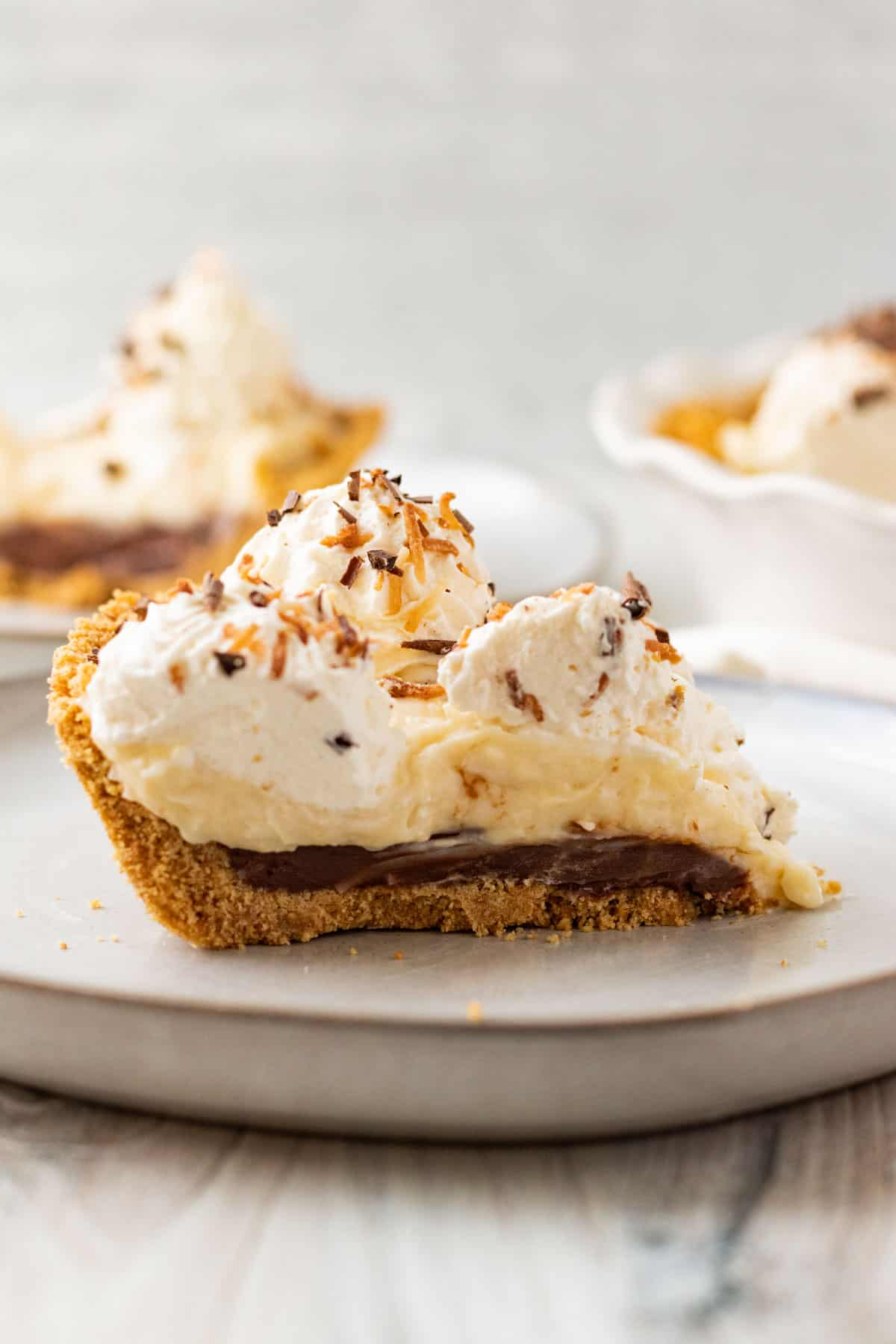 slice of chocolate coconut cream pie with whipped cream on a gray plate with another slice in background