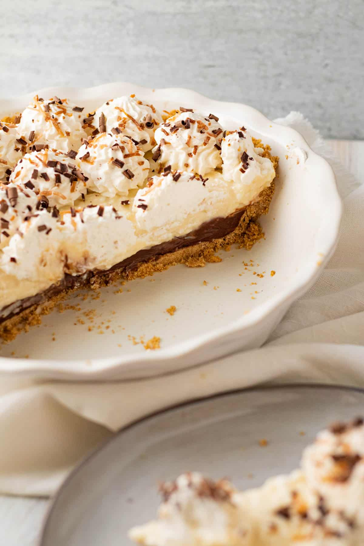 white pie dish with chocolate coconut cream pie filling half of dish and slice of pie on a plate in front