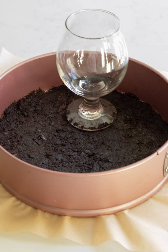 oreo crust being packed down into a pink springform pan with a glass