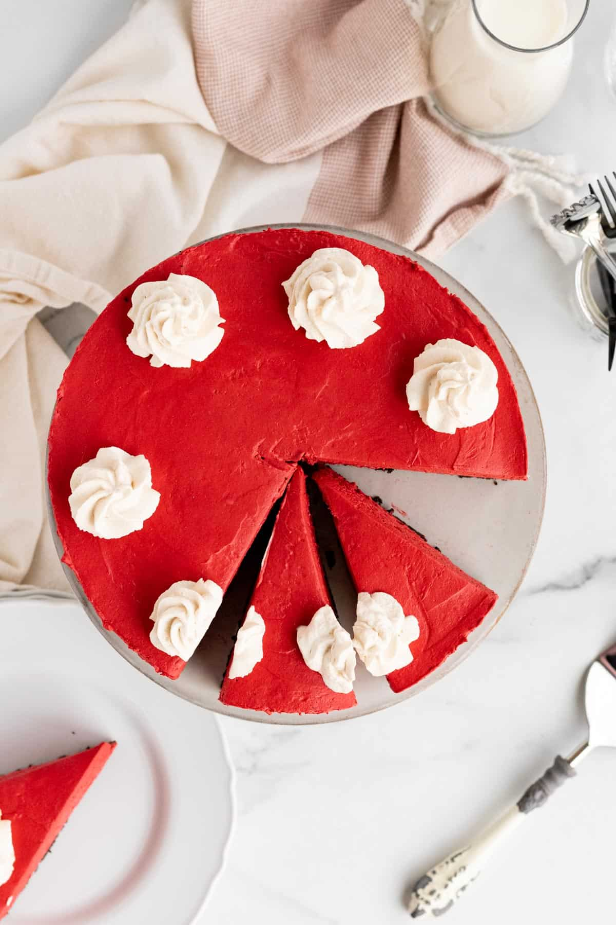 red velvet no-bake cheesecake with 2 slices cut and another slice on a white plate