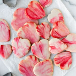 pile of red and pink marbled heart shaped sugar cookies on white parchment paper