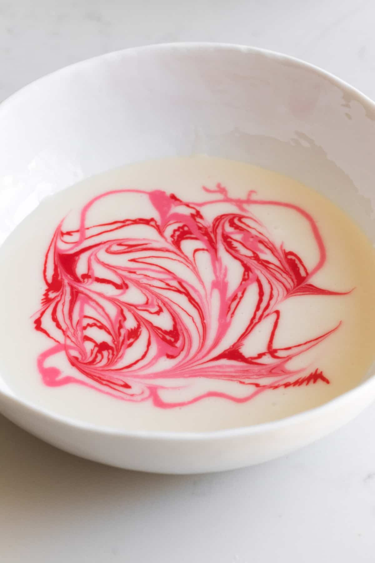 bowl of white icing with pink and red swirls in it