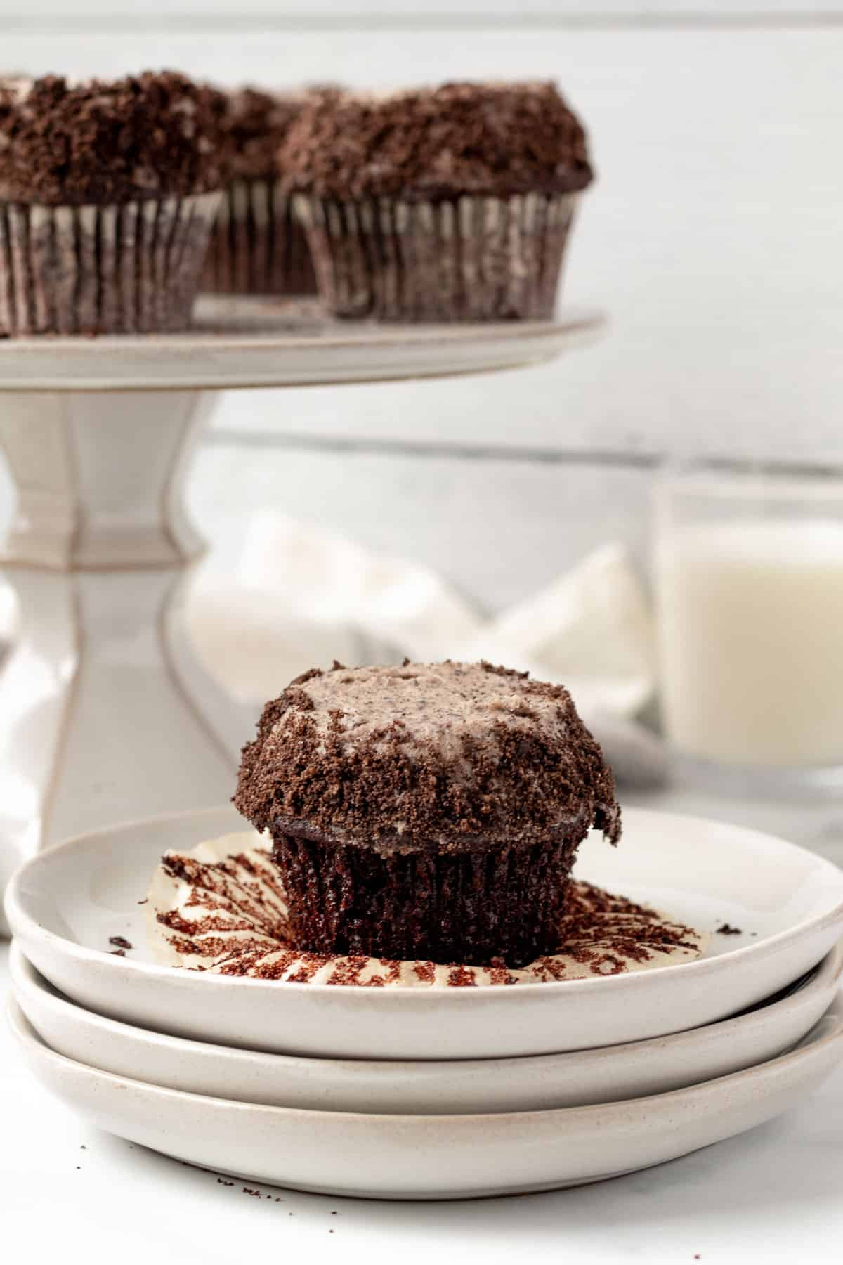 chocolate cupcake with oreo buttercream sitting on a stack of plates with glass of milk in background