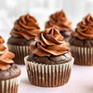 multiple chocolate cupcakes with chocolate buttercream sitting on a pink surface