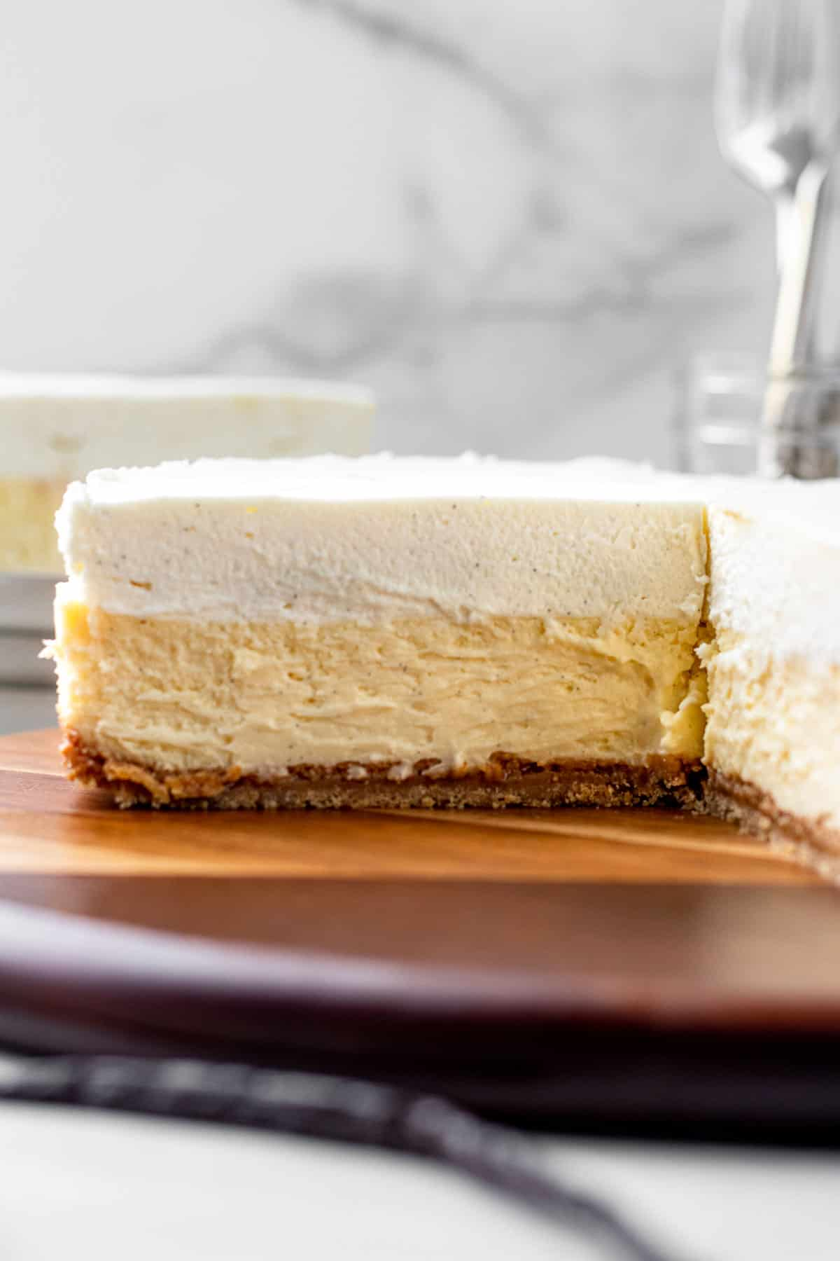 vanilla bean cheesecake sitting on wooden board showing layers of cheesecake and white chocolate mousse
