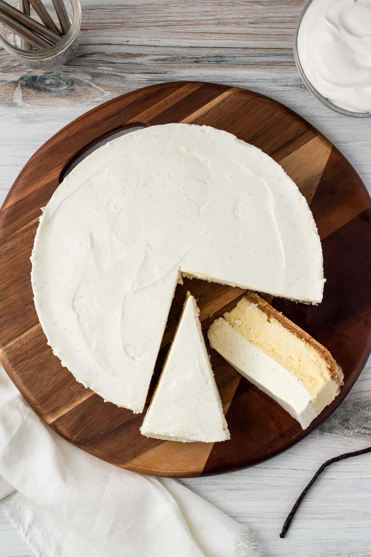 overhead view of a vanilla bean cheesecake with 2 slices cut out sitting on a round wooden board