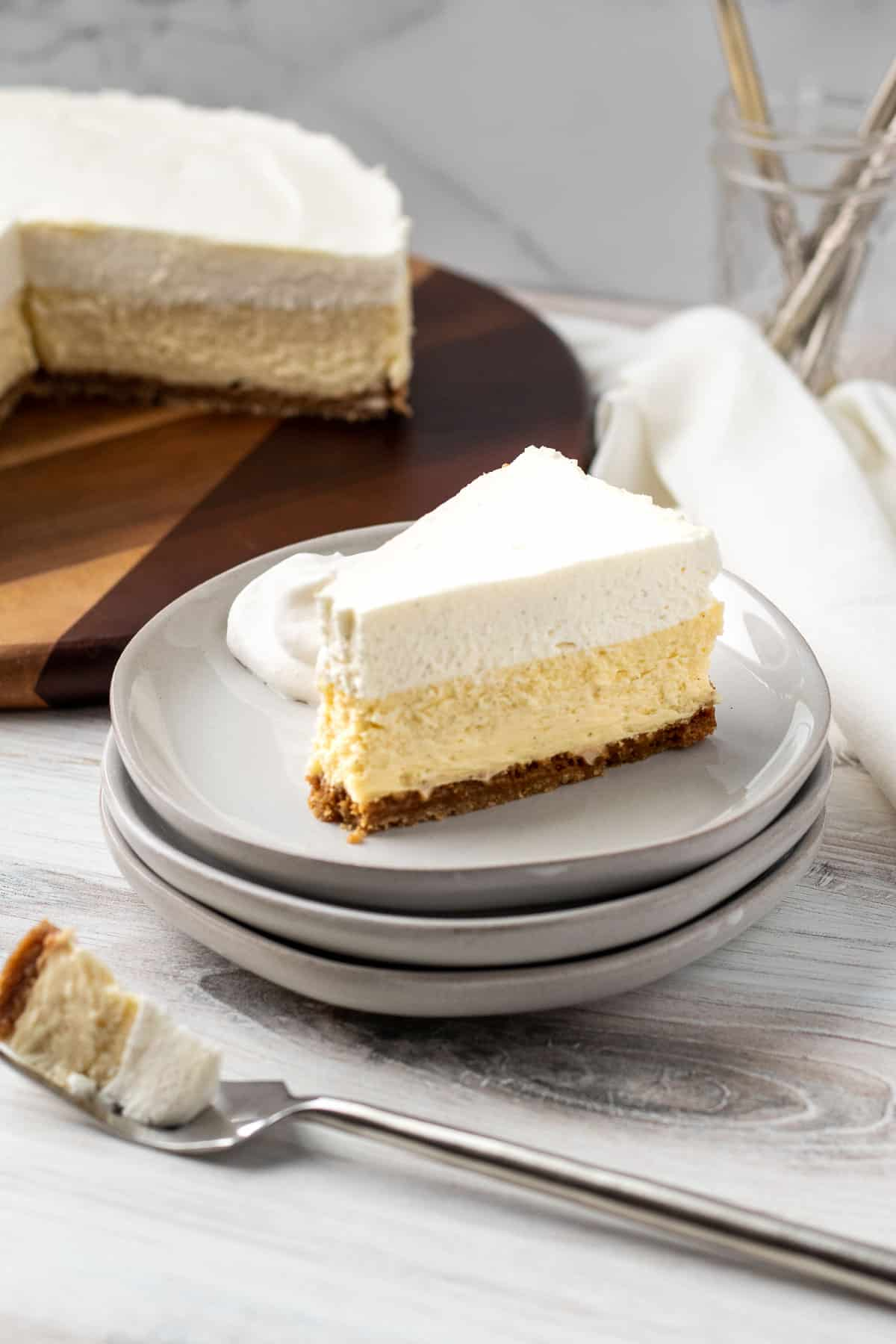 slice of vanilla bean cheesecake on stack of plates with bite of cheesecake on a fork in front of cake