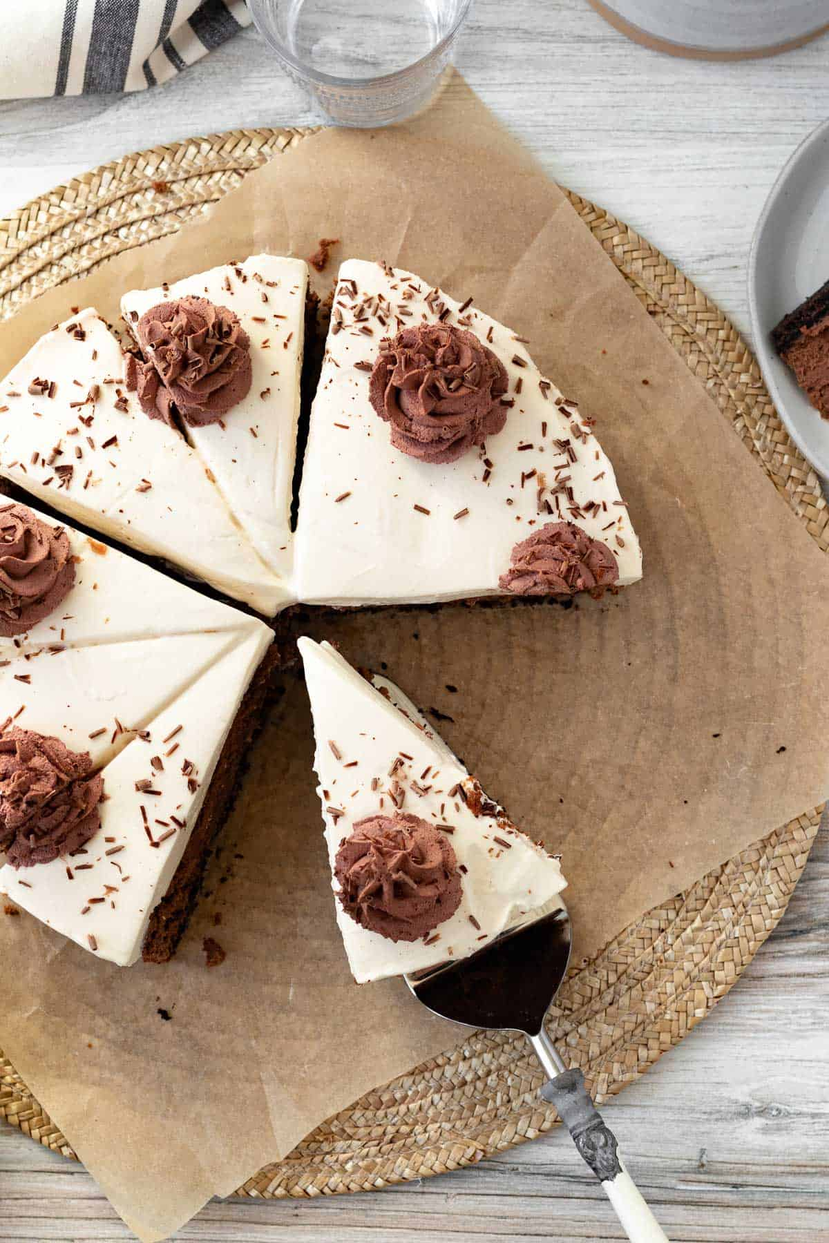 chocolate baileys cheesecake sitting on brown parchment paper with chocolate whipped cream swirls