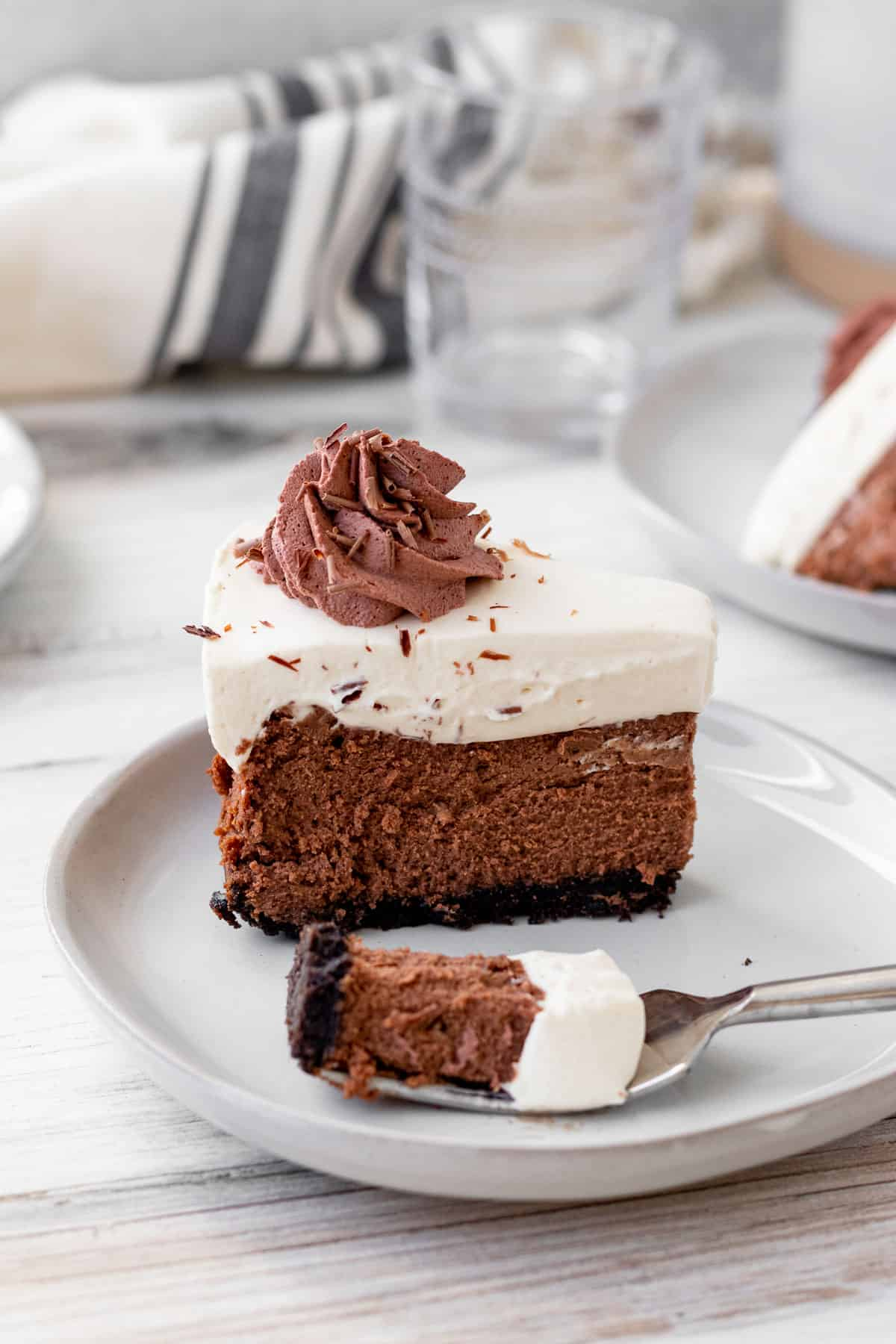 slice of chocolate baileys cheesecake on a plate with bite of the cheesecake on a fork
