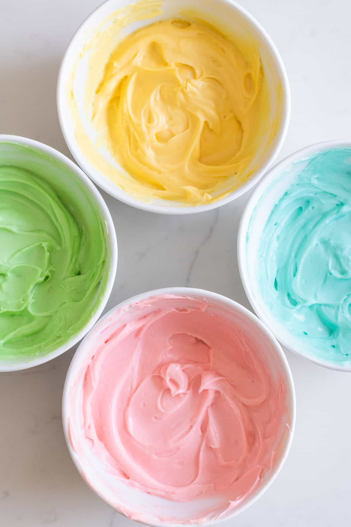 bowls of cream cheese filling dyed pastel colors