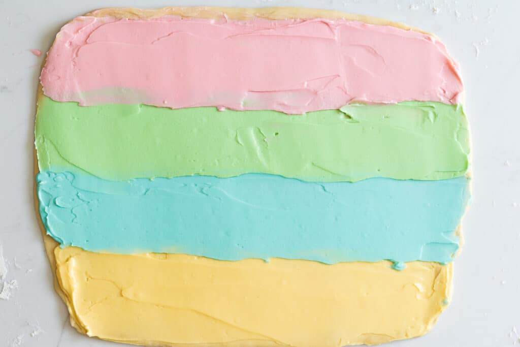 Babka dough rolled into a rectangle and spread with pastel colors in 4 horizontal lines
