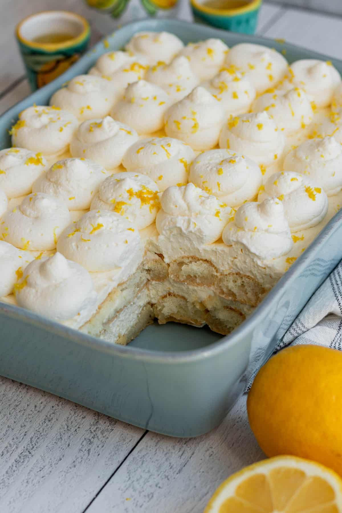 blue baking dish with layers of ladyfingers and lemon mascarpone with lemons to side of baking dish