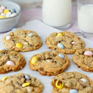 mini egg cookies on parchment paper with glasses of milk in background with bowl of mini egg candies