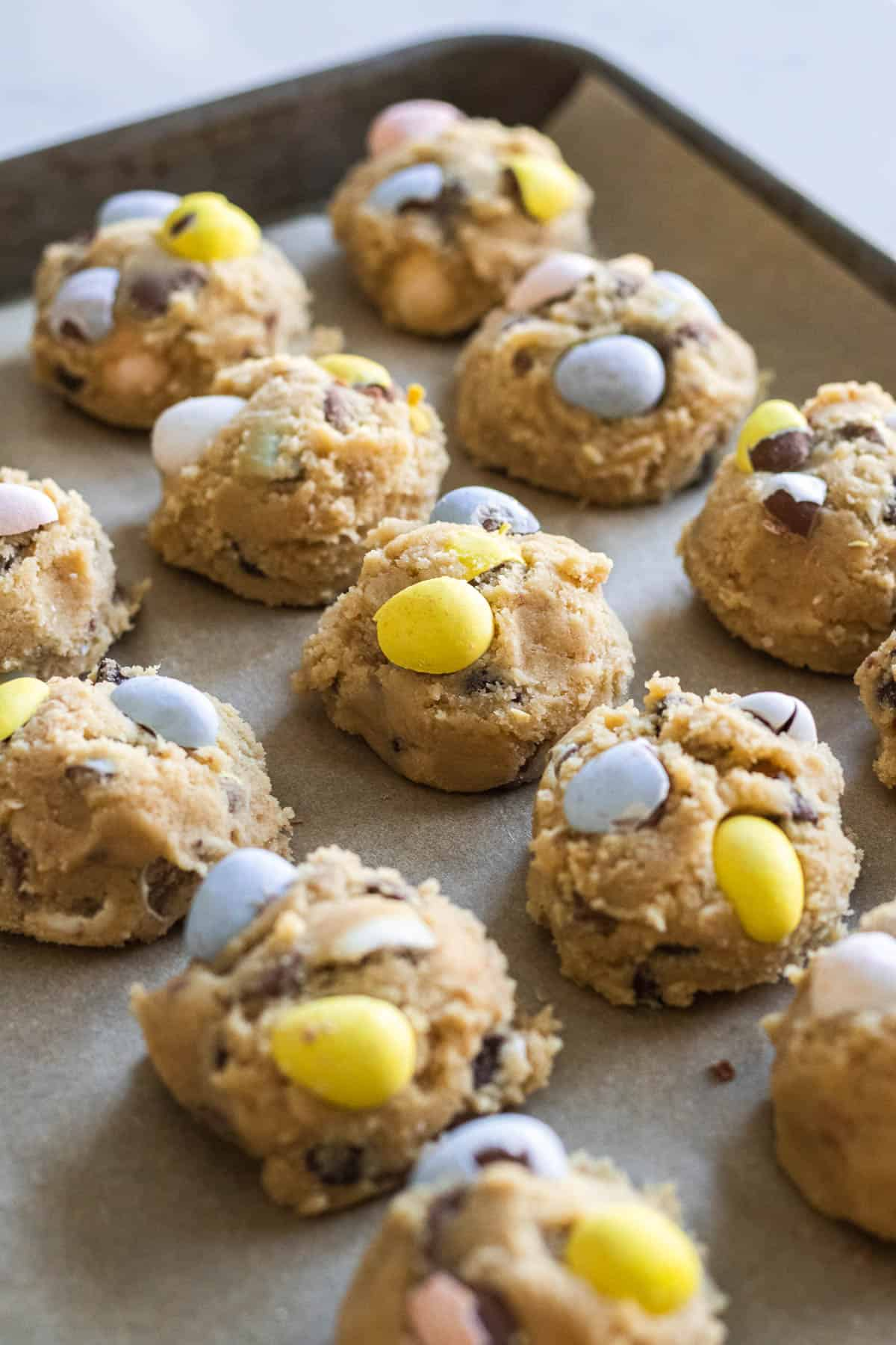 balls of cookie dough with mini egg candies on top