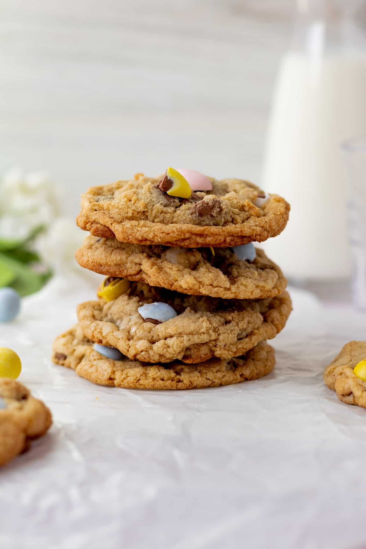 stack of mini egg cookies with glass pitcher of milk in background
