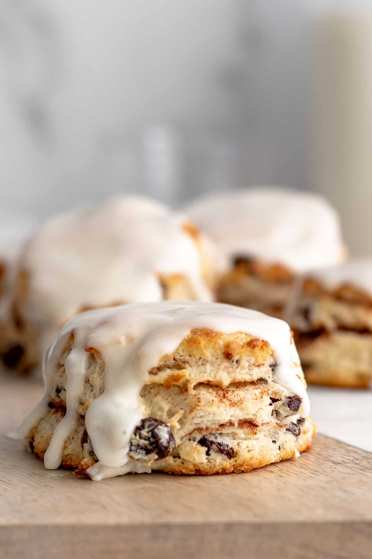 Cinnamon raisin biscuit with a white  glaze sitting on a wood board with more biscuits in the background