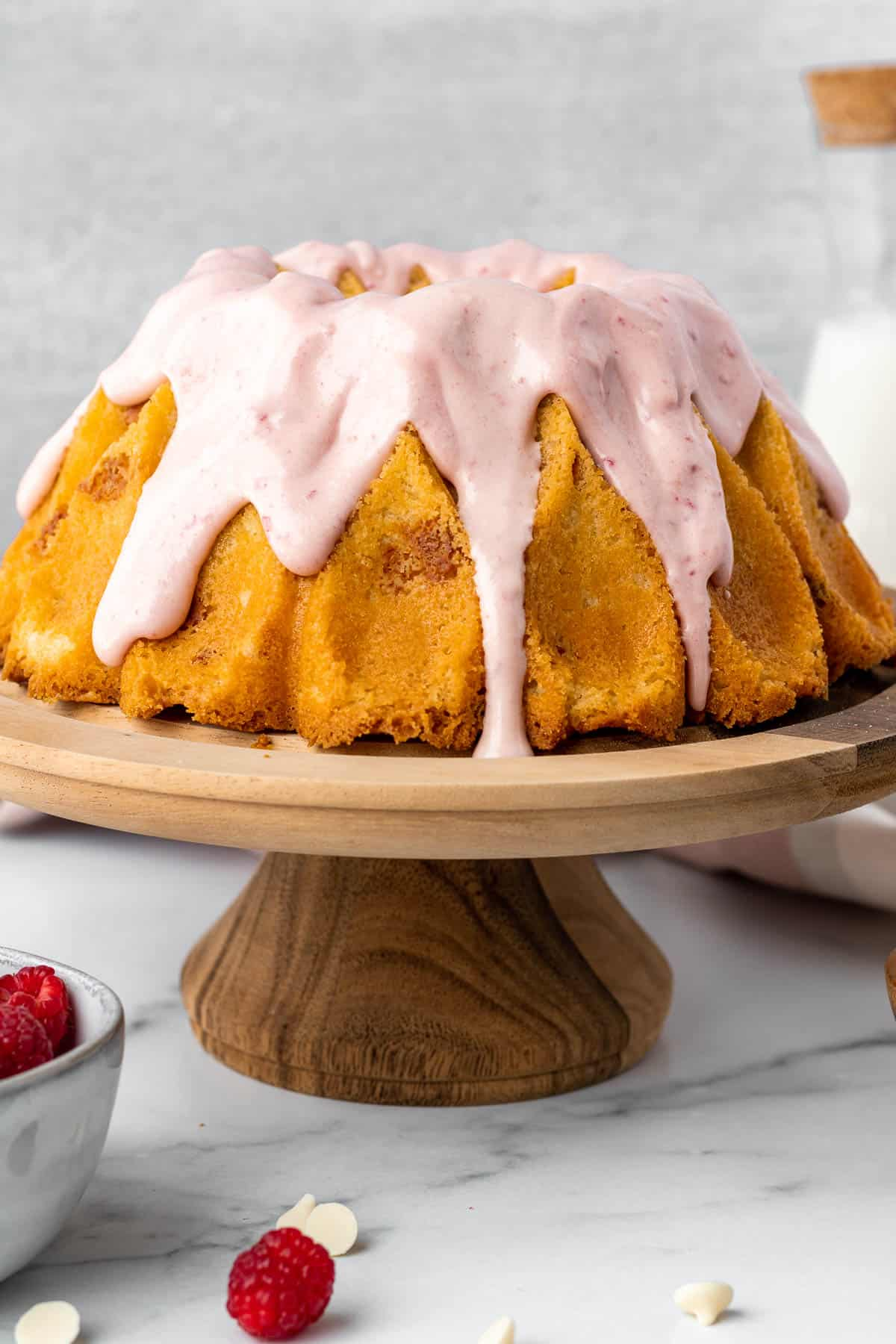 white chocolate raspberry bundt cake on a wood pedestal with bowl of raspberries in foreground and glass of milk in background