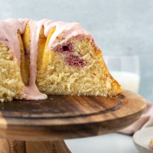 bundt cake with pink glaze on wooden pedestal with slice exposed and glass of milk in background
