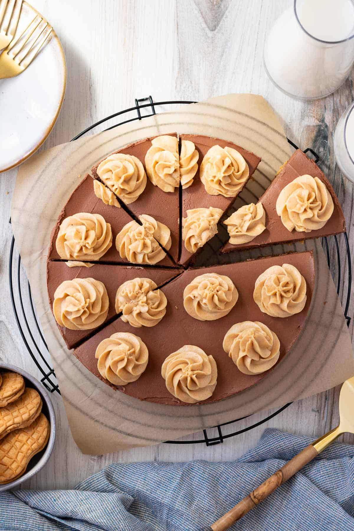 chocolate peanut butter cheesecake on top of a black wire cooling rack with a bowl of peanut butter cookies next to it