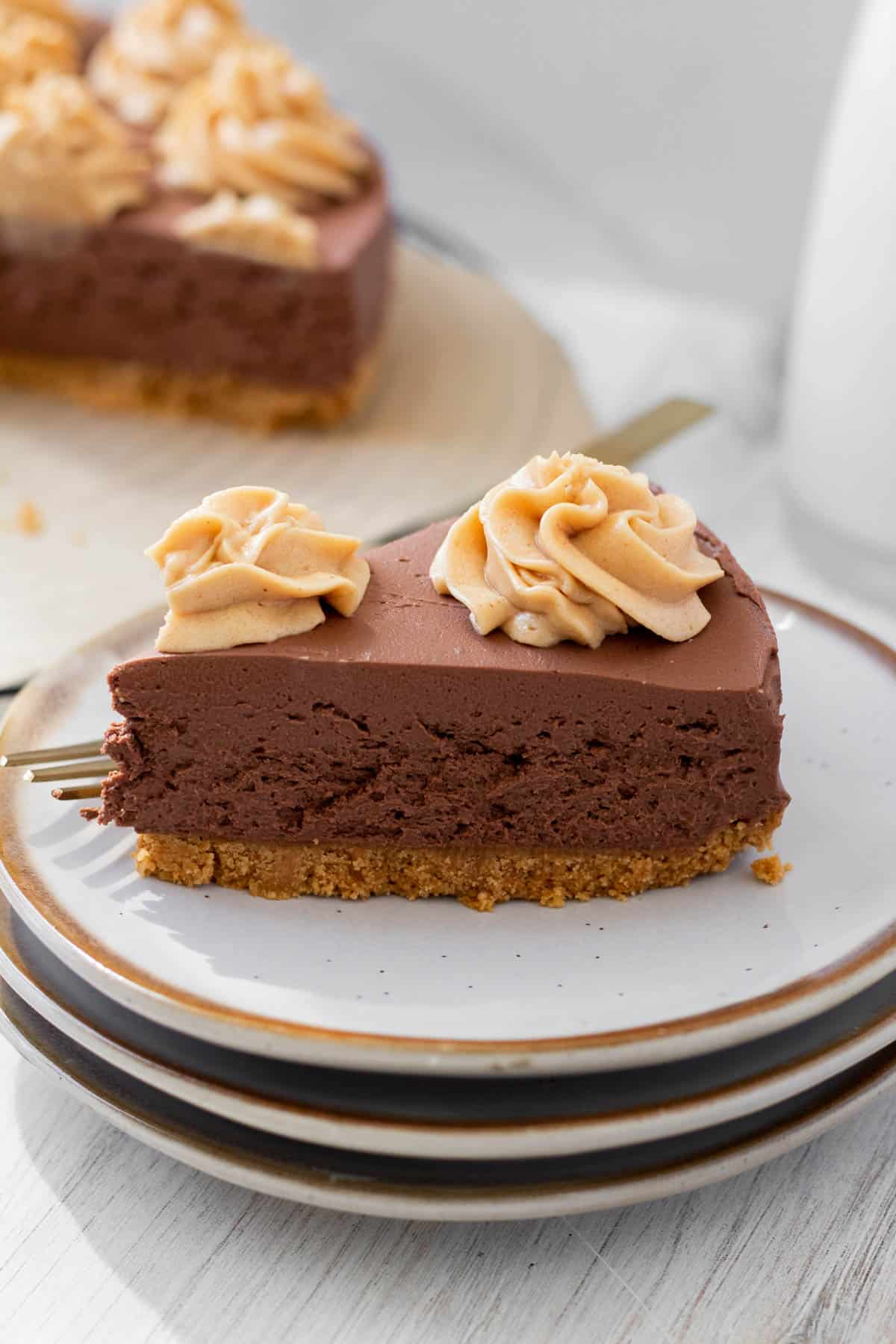 slice of chocolate peanut butter no-bake cheesecake on a white plate with a golf fork