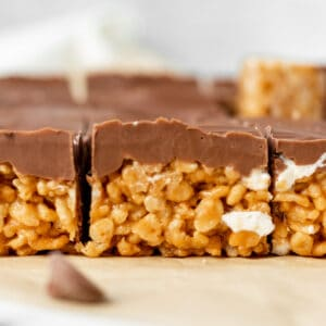 peanut butter rice krispie treats topped with chocolate sitting on brown parchment paper