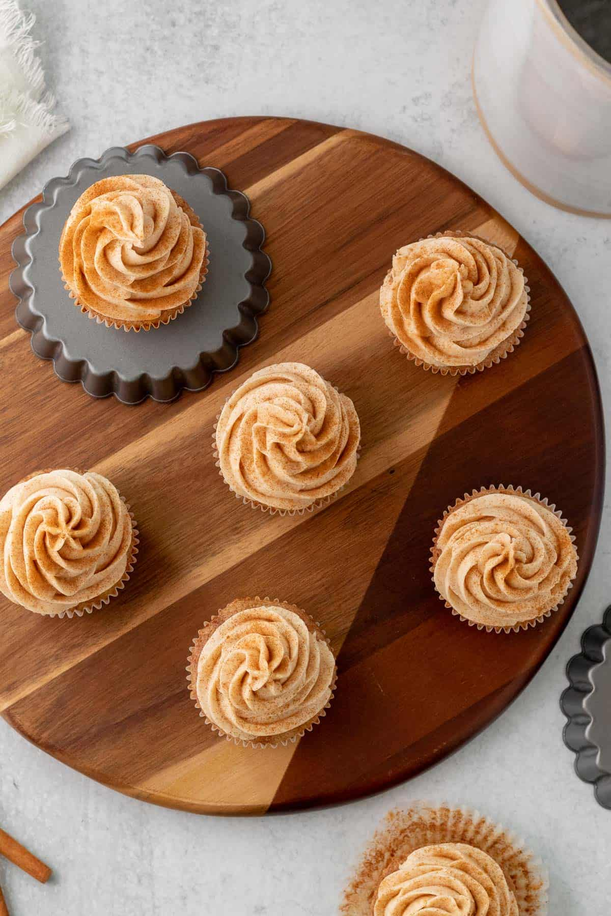 cinnamon cupcakes sitting on a round wood board