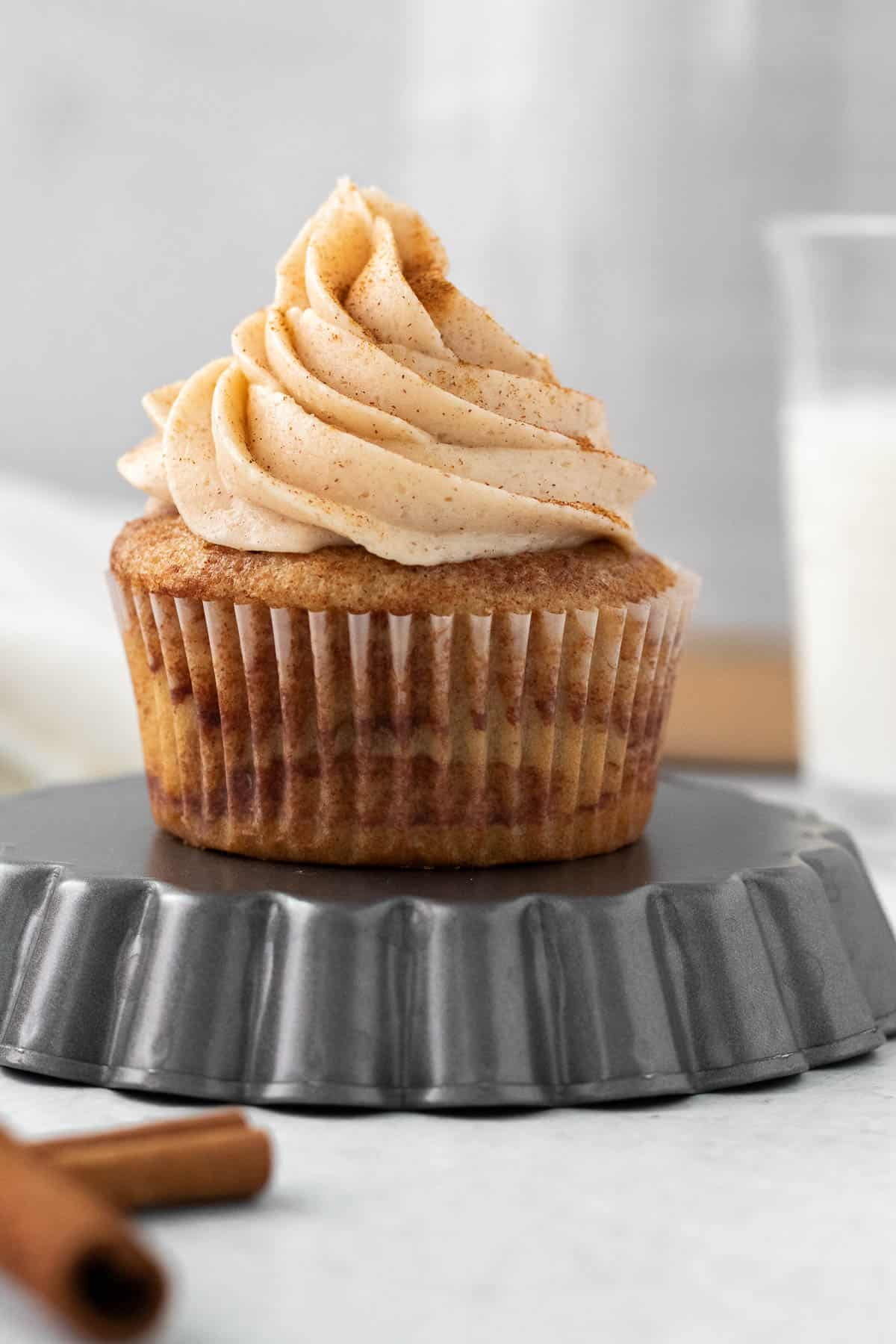 cinnamon cupcake with cinnamon buttercream sitting on an upside down tart pan with a glass of milk in the background