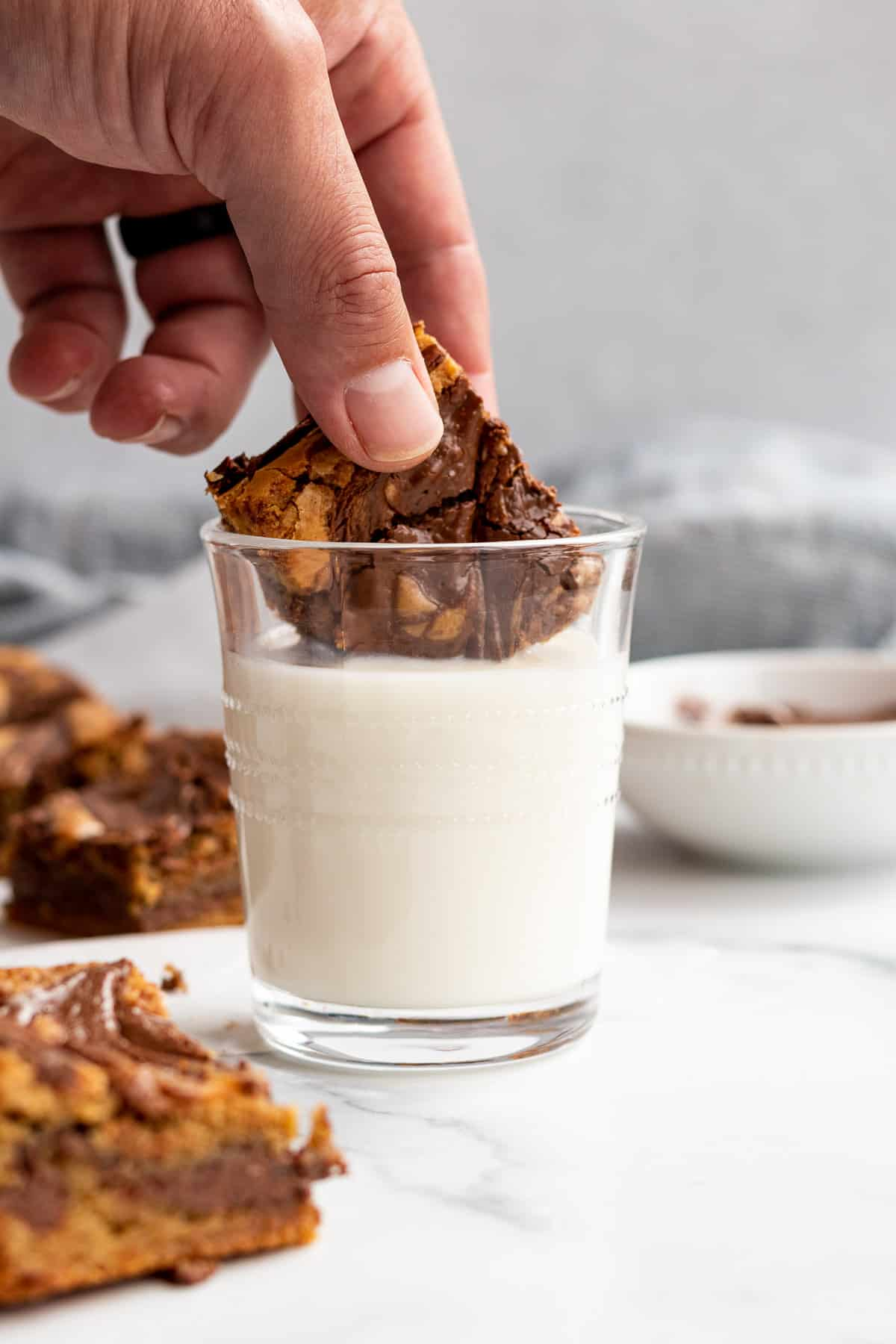 nutella blondie being dipped into a glass of milk