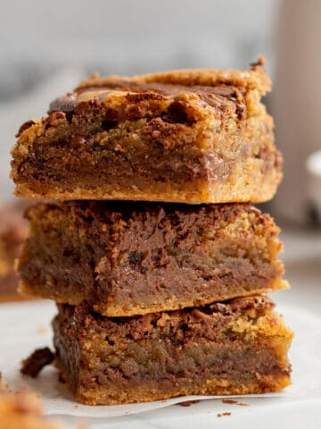 stack of 3 nutella blondies with white bowl and carafe in background
