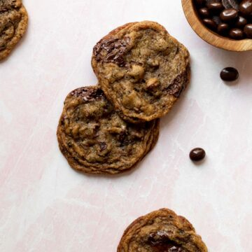 espresso chocolate chip cookies on a pink background with a small bowl of chocolate espresso beans