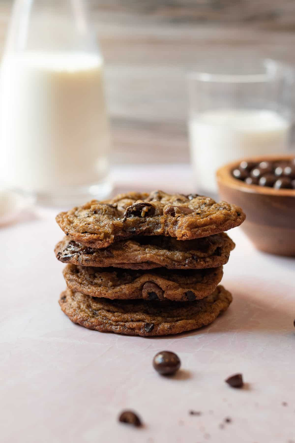 stack of espresso chocolate chip cookies with glasses of milk in the background