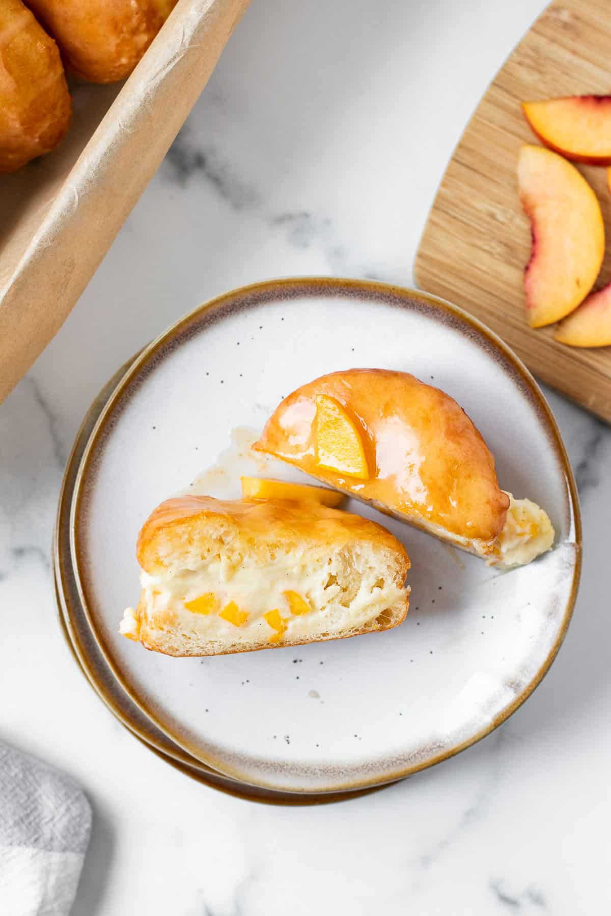 peach donut filled with cream split in half on a stack of plates with cutting board with peaches next to it