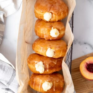 basket of peach doughnuts with cream filling