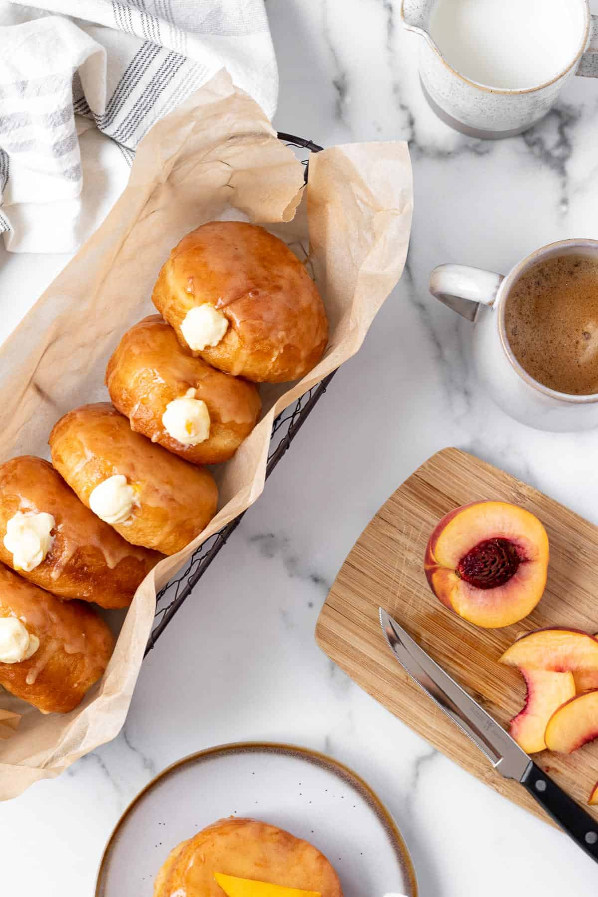 peach doughnuts with vanilla filling in a basket with cutting board with sliced peach