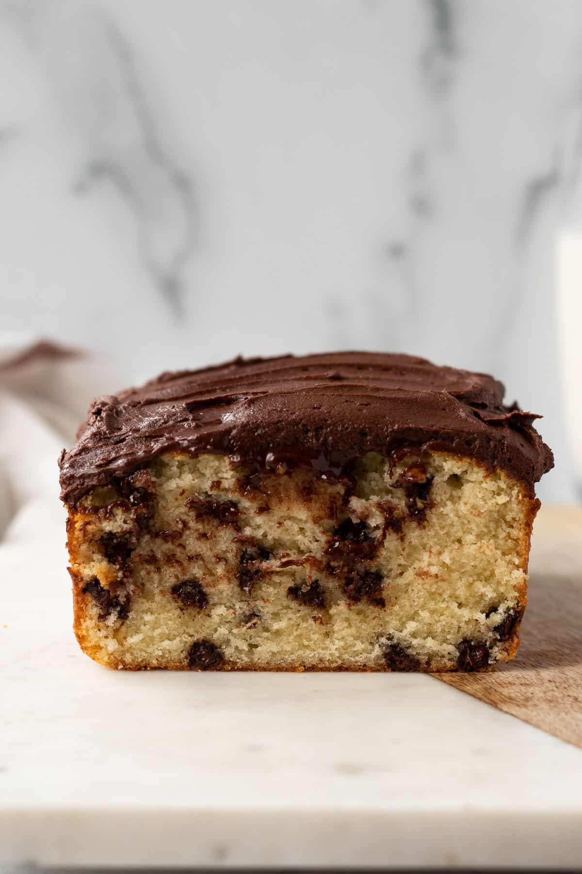 chocolate chip loaf cake frosted with whipped chocolate ganache sitting on a marble slab