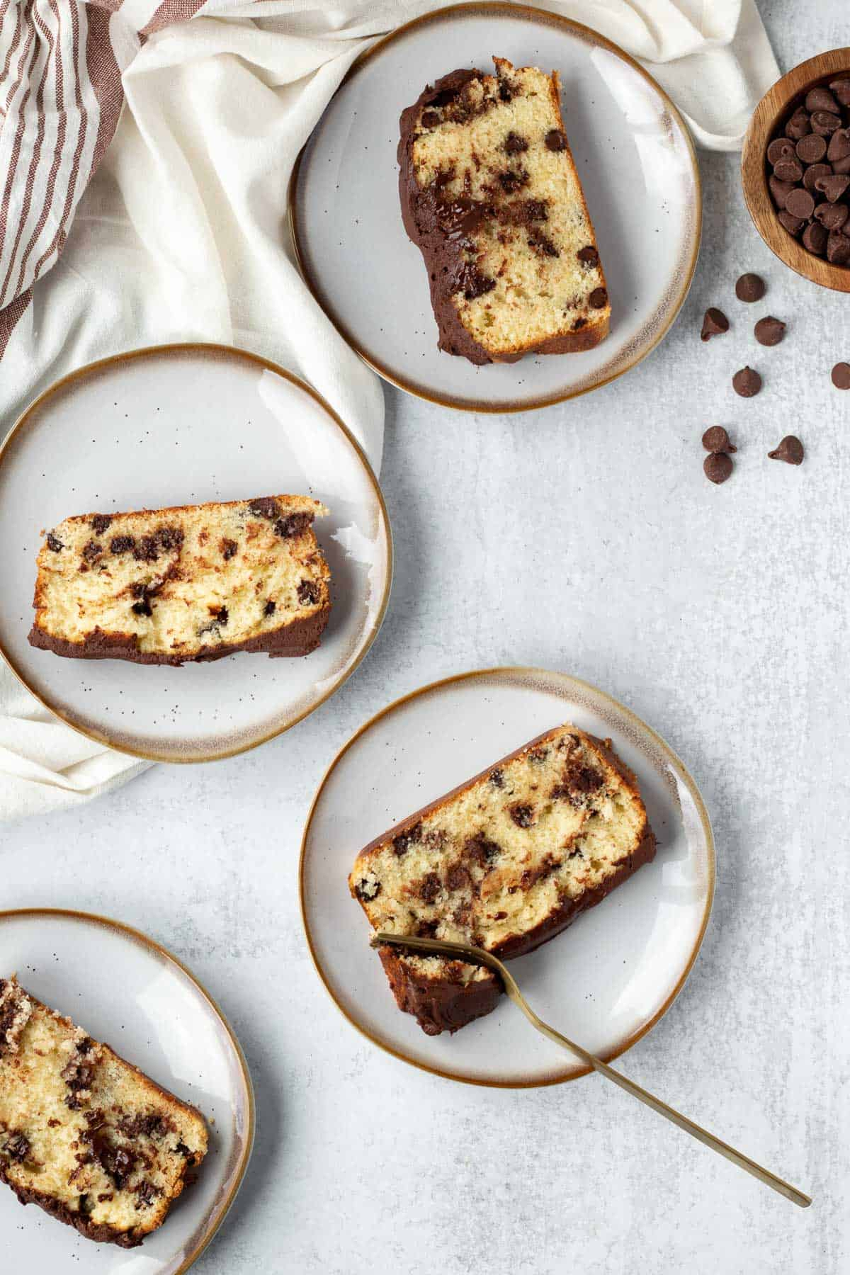 4 plates of chocolate chip loaf cake on gray background with a white linen and chocolate chips
