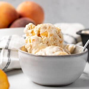 bowl of peaches and cream ice cream with peaches in background