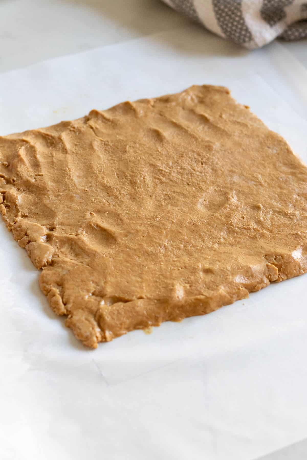 peanut butter filling rolled out into a square sitting on parchment