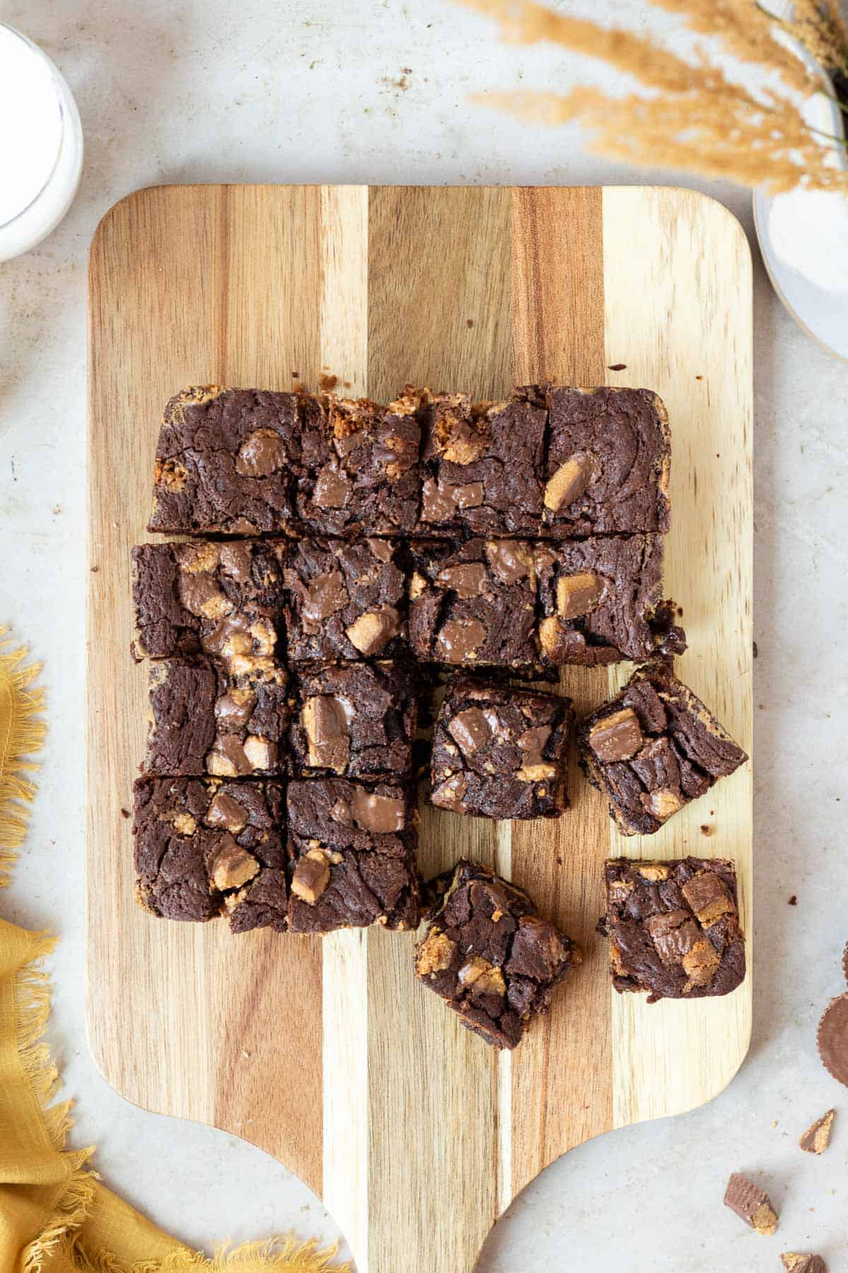 slab of peanut butter cup brownies cut into squares sitting on top of a wooden cutting board