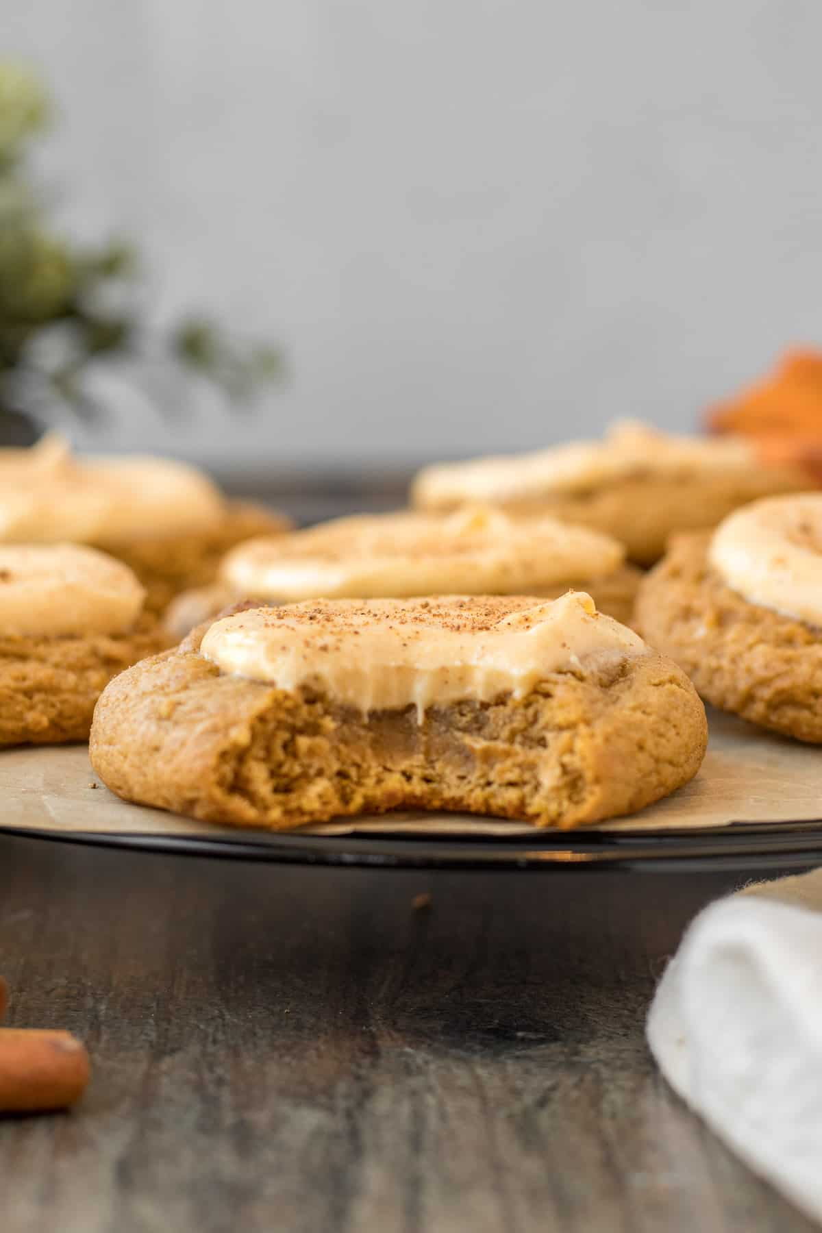 close up view of a pumpkin cookie with cheesecake filling with a bite out of it